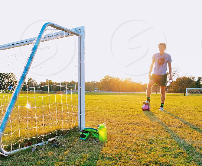 Soccer player training at dusk not giving up on his dreams.  photo