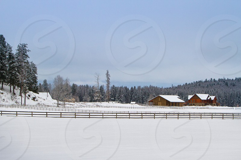 Home in snow with fence in rural area photo