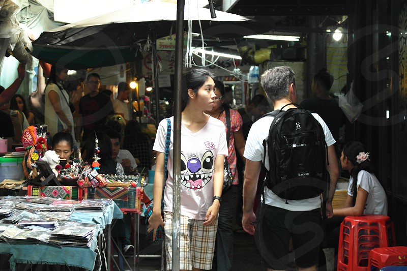 woman with stitch printed shirt walking at the market area photo