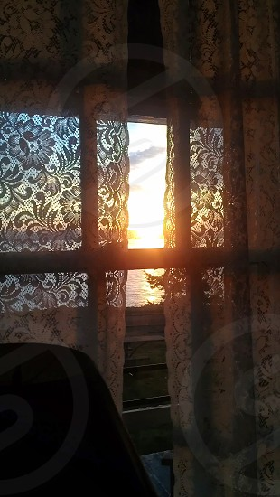 From the inside looking out.  Lace pattern sunrise photo