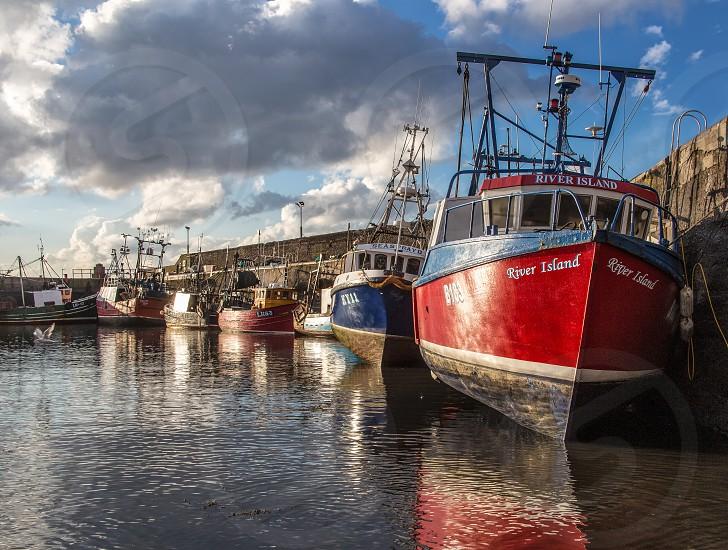 Fishing boats lined up along harbor wall. photo