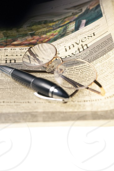 pen and glassesand newspaper over white glass table photo