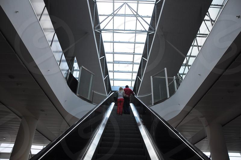 2 person riding an escalator photo