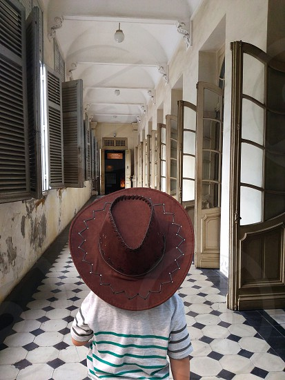 child wearing brow leather cowboy hat and gray and green stripe t-shirt standing in hallway photo