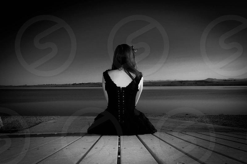 woman in black tank dress sitting on wooden pathway photo