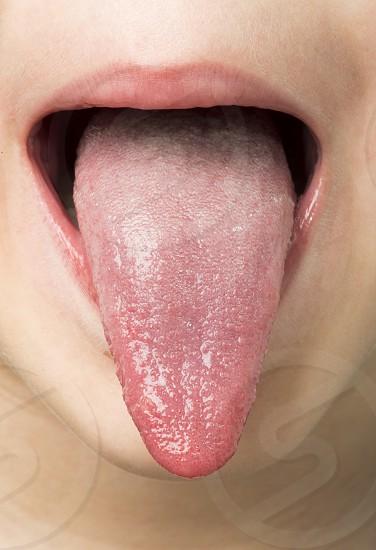 Human tongue protruding out. Child tongue. photo