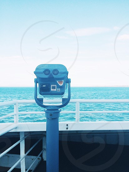 gray coin operated binoculars on viewing deck near blue ocean water under blue and white sunny cloudy sky photo