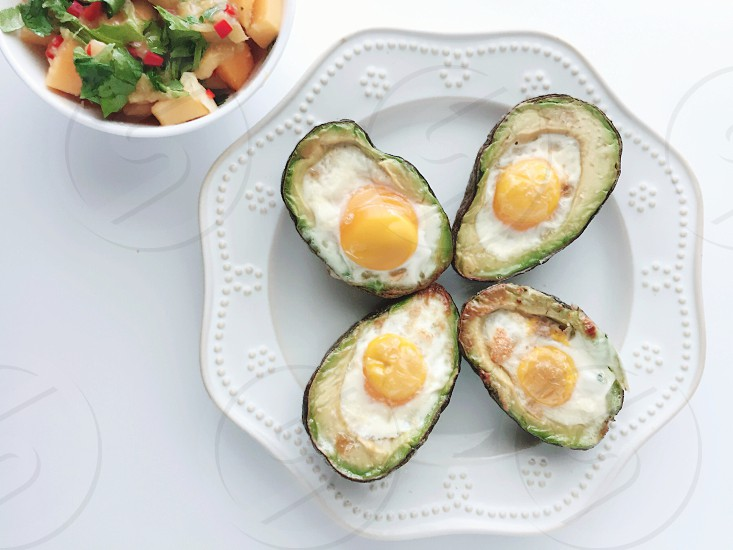 On the Table - Farm-fresh eggs baked in avocado halves on a white plate with mango salsa in a white bowl on a white background photo