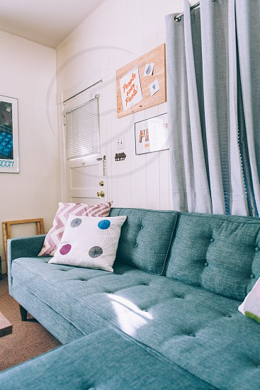 3 throw pillows on green padded couch photo