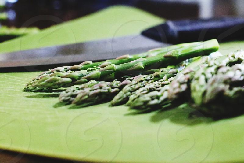 green asparagus near kitchen knife photo