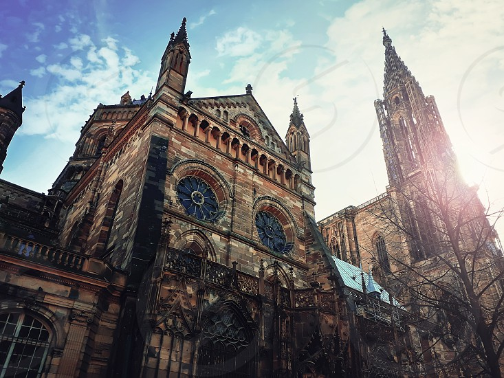 Side view of Roman Catholic Cathedral Notre Dame of Strasbourg in Alsace France. Beautiful sunny day with blue sky. Majestic gothic architecture outdoor facade. photo