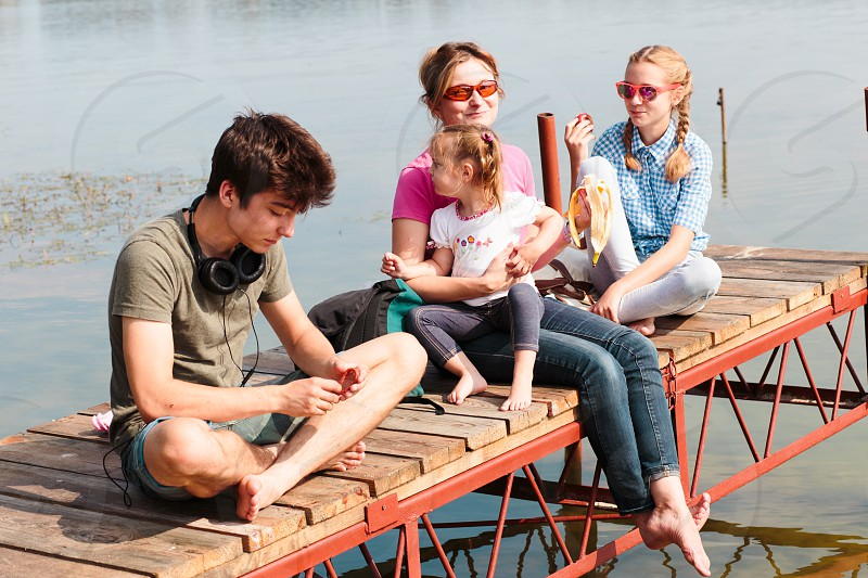 Family spending vacation time together having a snack sitting on jetty over the lake on sunny day in the summertime photo