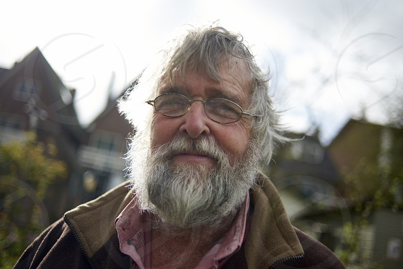 Portrait of a bearded elderly man looking into camera smiling with dirty hands from gardening photo
