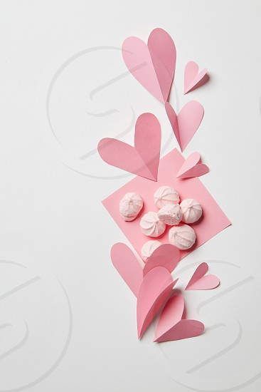 beautiful paper hearts and pink meringues in the corner of a white background photo