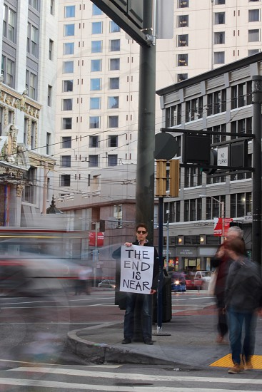 Man holding a sign that reads 'The End is Near' with life busting around him. photo