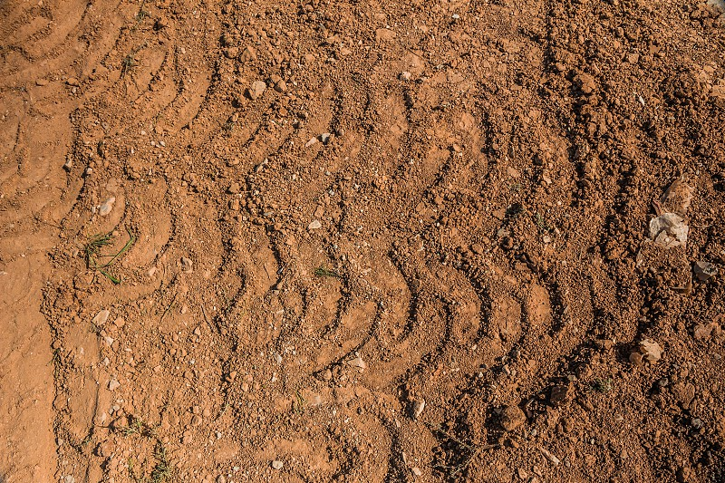 Texture of brown dirt with tractor tyre tracks. photo