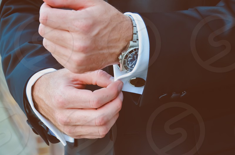 Businessman adjusting his sleeve. photo