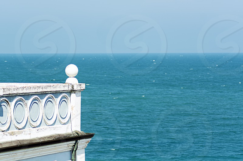 Ancient house with a decorated balcony overlooking the sea. Architecture and holidays. photo