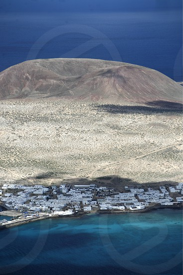 The  Isla Graciosa with the village of Caleta del Sebothe from the Mirador del Rio viewpoint on the Island of Lanzarote on the Canary Islands of Spain in the Atlantic Ocean. on the Island of Lanzarote on the Canary Islands of Spain in the Atlantic Ocean.