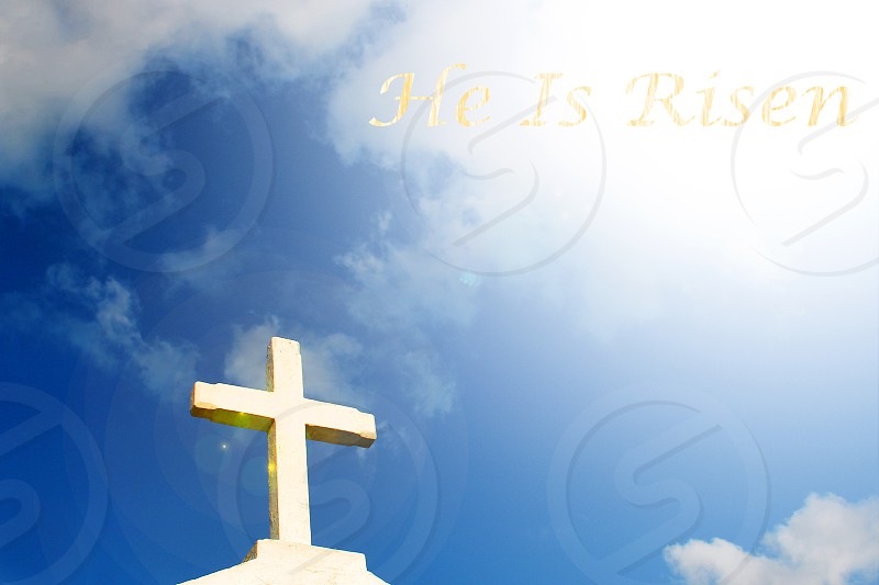 """White cross with the words """"He is Risen"""" photo"""