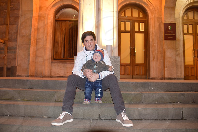 man holding baby while seated on concrete stair photo photo
