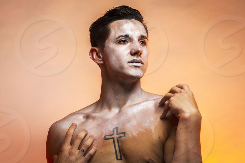 man topless with cross tattoo photo