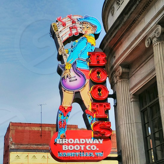 neon sign cowgirl boots and guitar photo