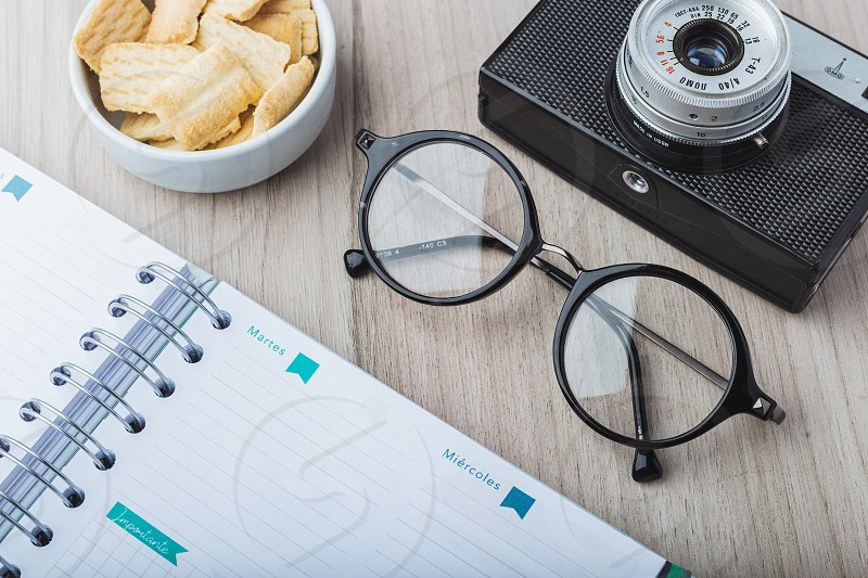 Woman glasses with planner cookies and camera photo