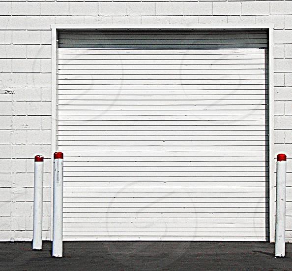 White metal garage door on a white building photo