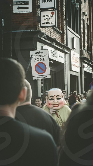 white male masked man in crowded place near brown bricked wall building with outer controlled zone signage photo