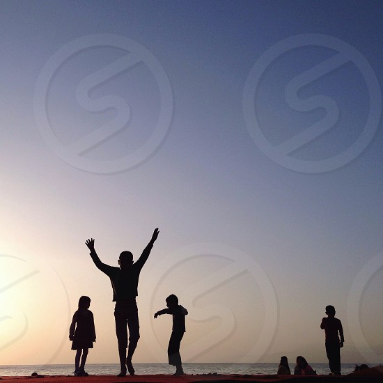 4 persons silhouette on beach photo