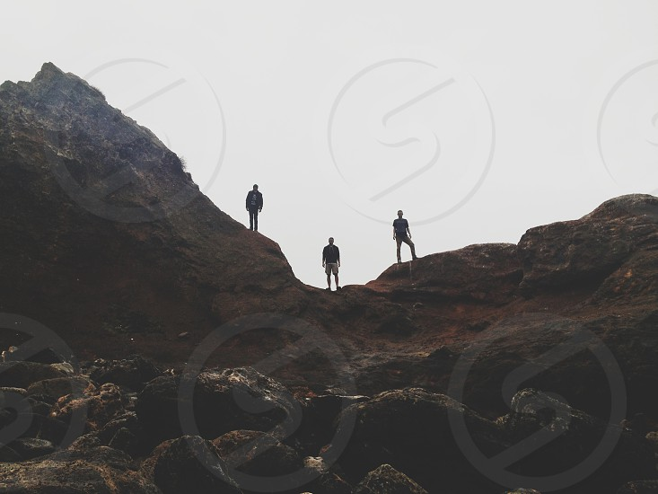 three silhouetted figures standing on a rocky ridge photo