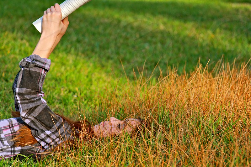 woman lying on green grass holding book photo
