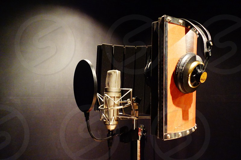 gold-colored condenser microphone with black pop filter and headphones photo