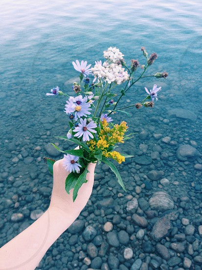 Wildflower bouquet held over lake water photo