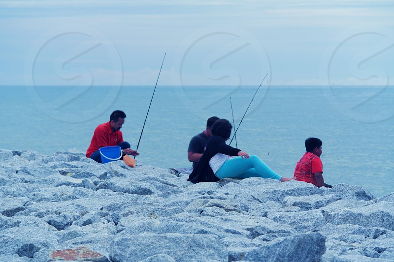 4 people sitting on white rock fishing during daytime photo