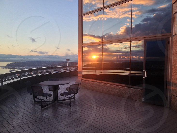 table on deck outside mirrored building at sunset photo