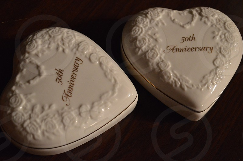 2 white 50 anniversary heart case on brown desk photo