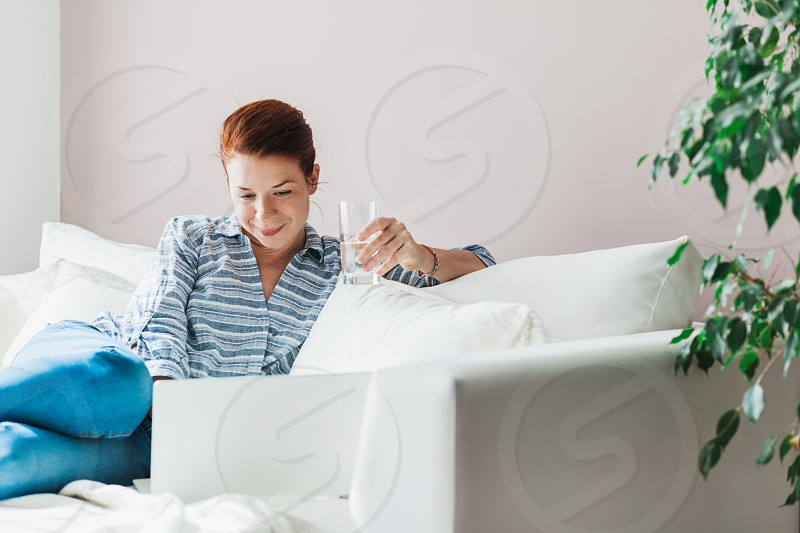Young woman working on a laptop in the living room photo