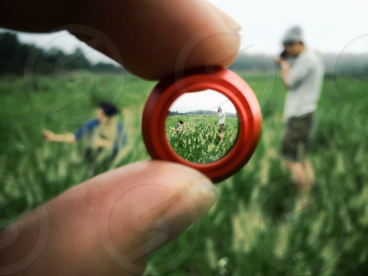 person holding red rim small magnifying glass viewing green field and kneeling woman and standing man photo