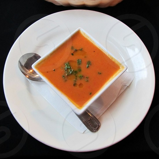 Tomato bisque in square bowl on white plate wth spoon on black tablecloth photo