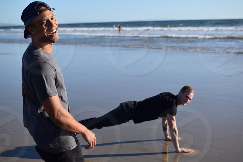man in push up position beside man wearing gray t-shirt during daytime photo