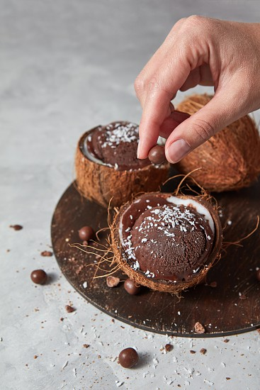 Chocolate brown homemade dessert in a coconut shell with girls hand decorating ice cream on a gray concrete background with place for text. Summer dessert for vegetarian. photo