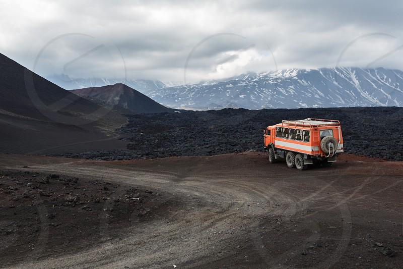 KAMCHATKA PENINSULA RUSSIA - JUNE 24 2016: Russian expedition truck KamAZ (6-wheel drive) on mountain road on background of lava fields and volcanoes. Eurasia Far East Russia Kamchatka Region Klyuchevskaya Group of Volcanoes. photo