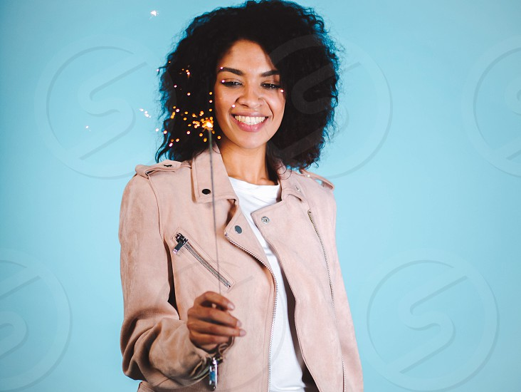 Sparkling Bengal fire in african american woman's hand on blue background. Christmas Holiday Concept. Young pretty girl with afro hairstyle celebrating smiling enjoying time photo