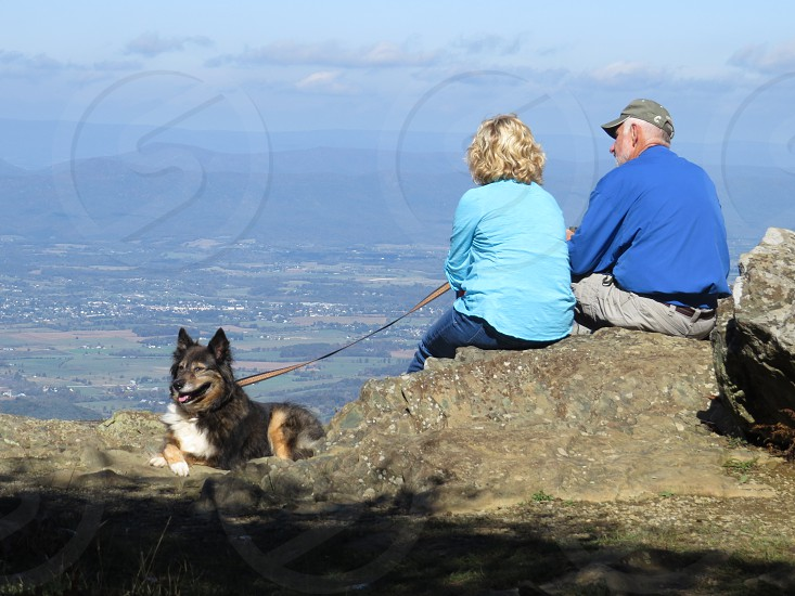 Man and woman with dog after hiking photo