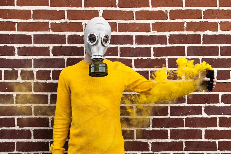 person wearing yellow long sleeved suit and gas mask holding yellow smoke grenade and standing near the photo