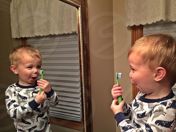 Child playing with toothbrush in mirror photo