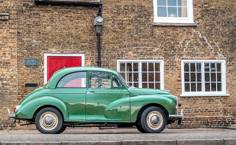 Retro vintage classic car past old fashion morris minor street cityscape windows red door ironworks photo