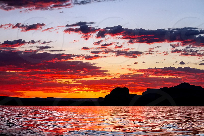 Calming silhouette sunset of Lone Rock in Wahweap Bay of Lake Powell in Arizona.   The sky has scattered clouds lit up in reds and pinks that reflect on the smooth water below. photo